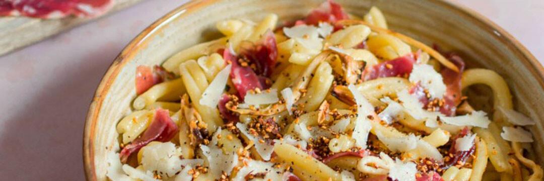 Strozzapreti met oesterzwammen, coppa, truffelpecorino en gekaramelliseerd sesamzaad