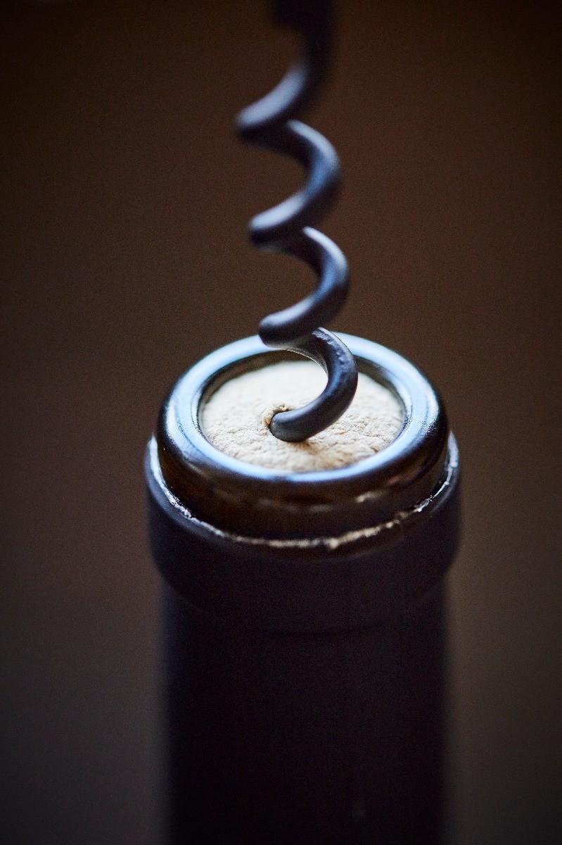 bouteille de vin qui est en train d'être débouchonnée